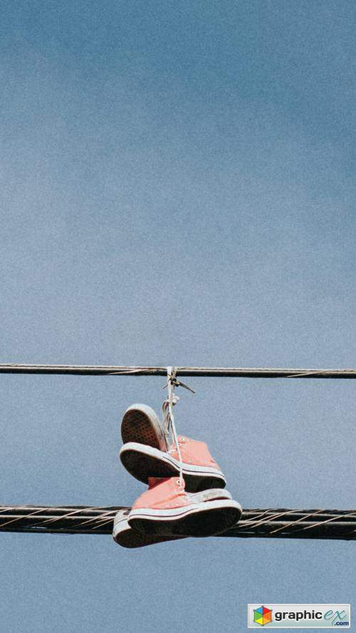 Pink sneakers hanging on an electricity line in downtown LA mobile wallpaper