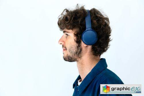 Cheerful man listening to music through headphones in a white background