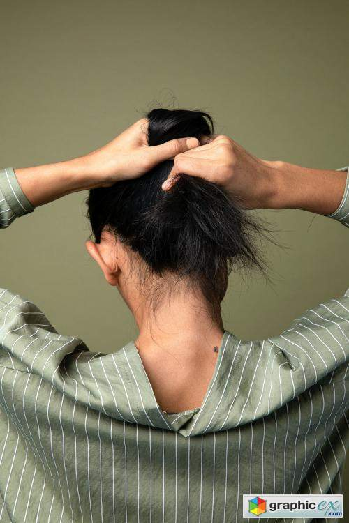 Rear view of a woman putting her long hair up